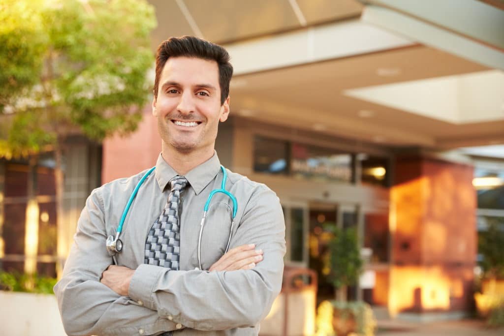 Portrait Of Male Doctor Standing Outside Hospital